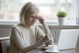 Older woman rubbing her eyes in front of lap top