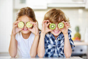 Young girls holding sliced veggies up to their eyes like glasses