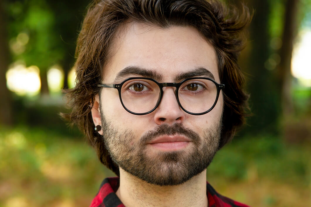 Young man with facial hair and glasses outside