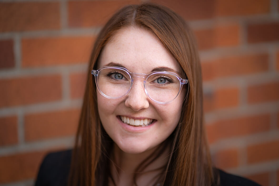 Smiling woman with round glasses posing against brick wall