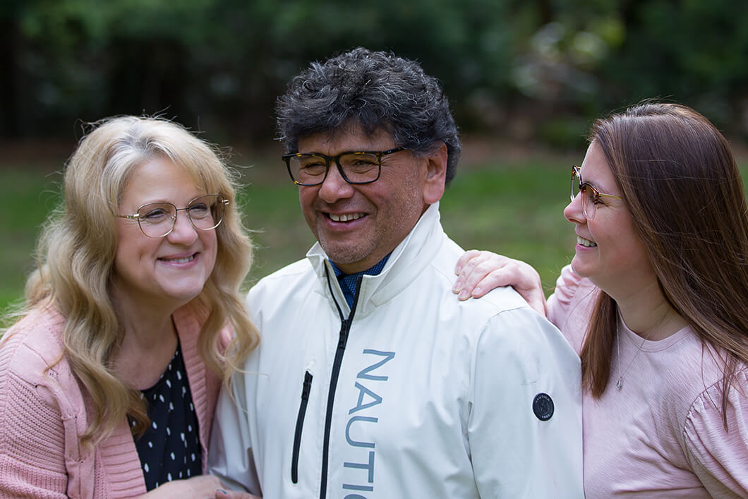 Two women and a man wearing glasses outside