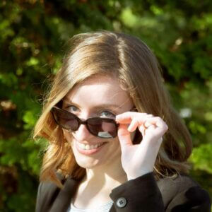Young woman looking over sunglasses