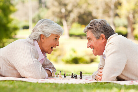 Older couple playing chess in park