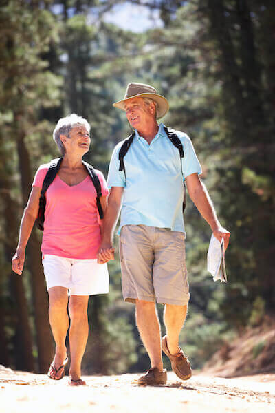 Happy mature couple hiking in summer