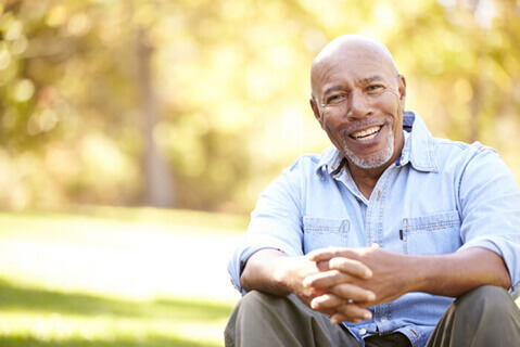 African American man sitting outside smiling at camera