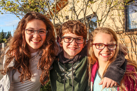 Three young friends wearing glasses