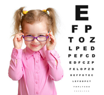 Little girl with glasses next to eye chart