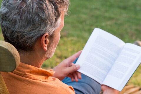 Man reading book outside