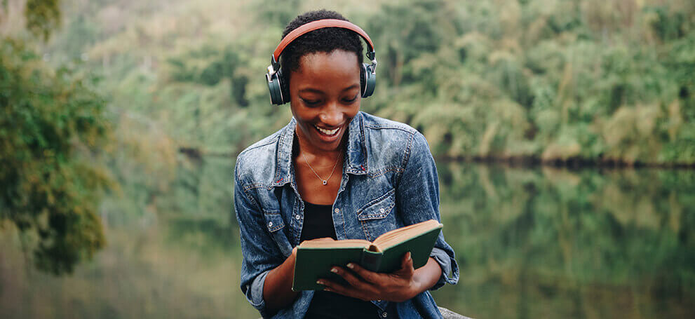 Woman reading with headphones next to lake
